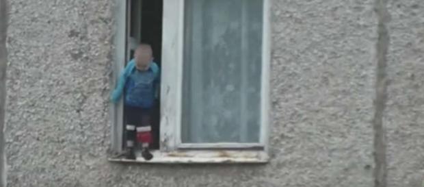 Copilaş pe pervazul unei fereastre de la etajul 8