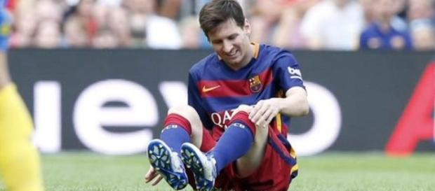 Lionel Messi attending to leg during a game