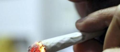 Fumatore mentre si accende uno spinello