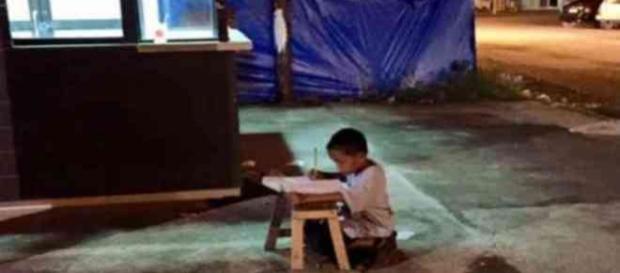 Menino estuda nas ruas por não ter luz em casa
