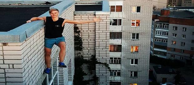 Jovem pendurado no alto de um prédio