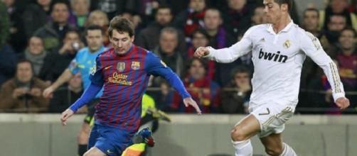 Messi y Cristiano disputan un balón
