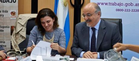 Lucresia Cardoso y Carlos Tomada dando la firma