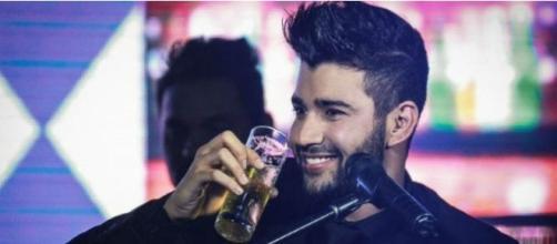 Gustavo Lima com copo de bebida alcoólica em show