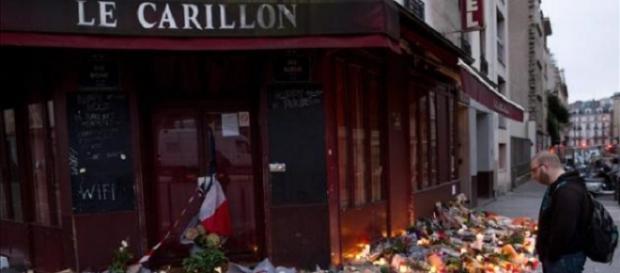 Un paseante mira las flores dejadas en Le Carillon