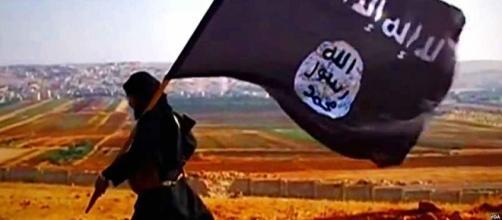 Militante del Daesh portando su bandera