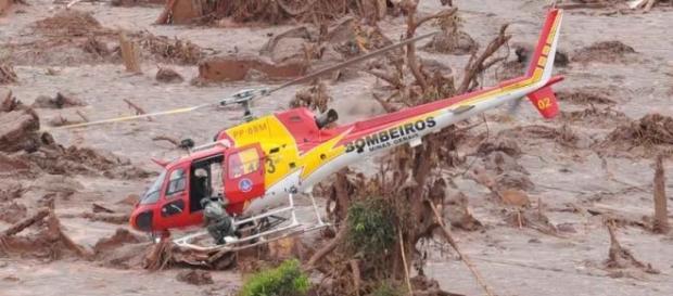 Helicóptero sobrevoando a área atingida pela lama