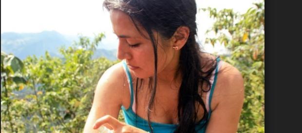 Mulher utilizando repelente para afastar mosquitos