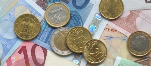 Un'immagine di banconote e monete in euro
