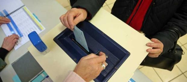 Una mujer introduce su voto en una urna.