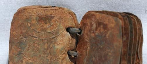 Livros de metal com inscrições bíblicas