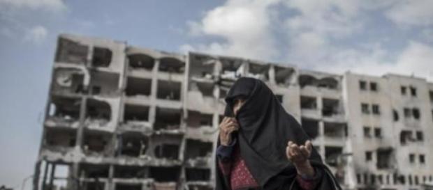 Edificio y mujer desolados por los ataques