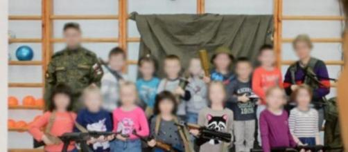 Les enfants posent avec des AK-47.