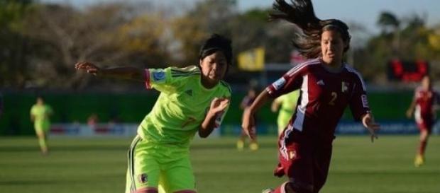 Dos mujeres practicando fútbol femenino