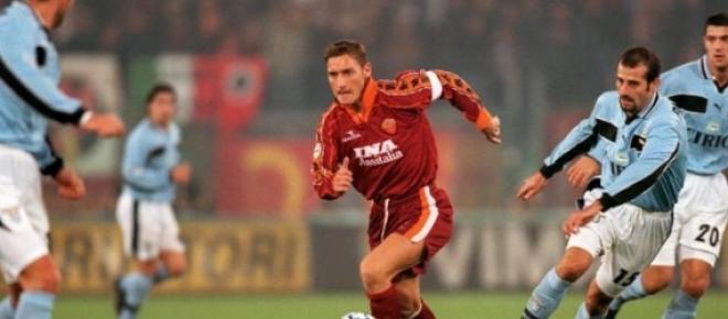 Totti conduce el esférico ante la mirada de cuatro jugadores celestes de la Lazio. En un derbi del pasado siglo en el Olímpico de Roma. El duelo de máxima rivalidad en el balompié de la capital de Italia.
