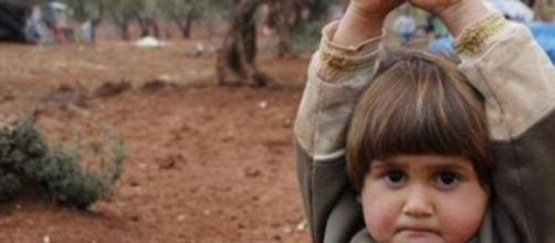 Criança em gesto de rendição