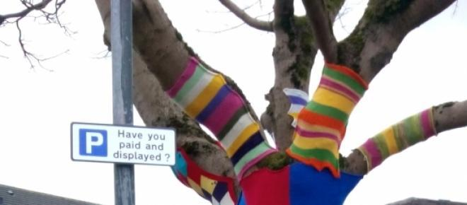 A photo of a tree decorated with knitting to celebrate the saving of the market ground from developers.