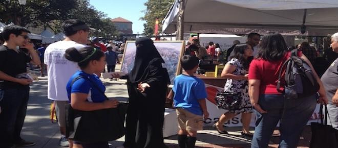 A completely veiled woman answers questions at the Quran booth, LA Times Festival of Books.