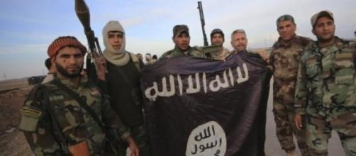 Militantes do EI exibem a bandeira do grupo