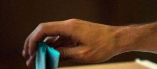 Un elettore depone la scheda nell'urna