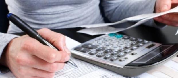 Calcolatrice alla mano per calcolare quanto pagare