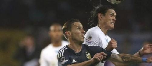Lucas Biglia luchando el balón con Cavani