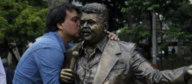 Carmelo Maia beija a estátua do seu pai na Tijuca