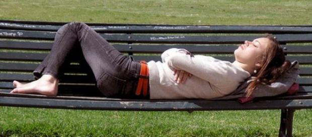 Persona durmiendo en el banco de la plaza.