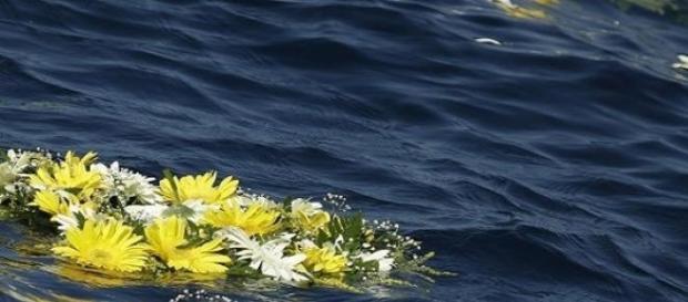 Corona di fiori per i migranti morti in mare.