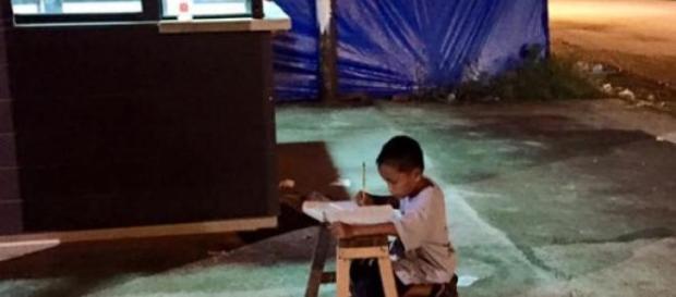 Menino aproveita a luz da rua para estudar