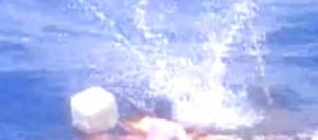 Hombre busca subir a bote en medio de disparos