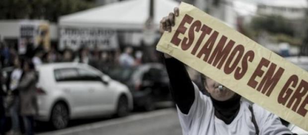 Manifestante exibindo faixa estamos em greve