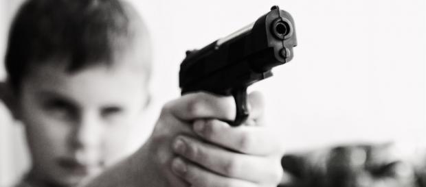 Copil cu o armă de foc în mână
