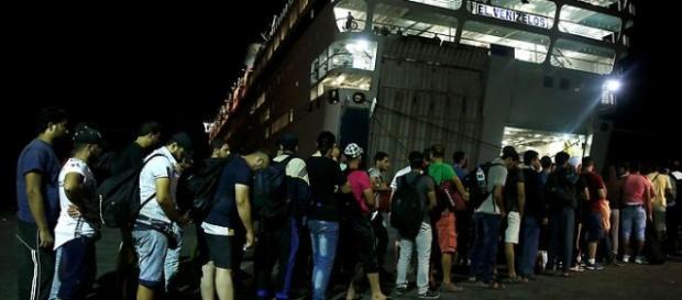Profughi in fila in attesa di farsi registrare