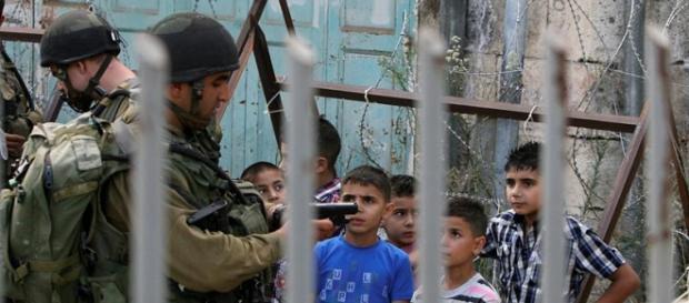 Militar israeli indagando a niños palestinos