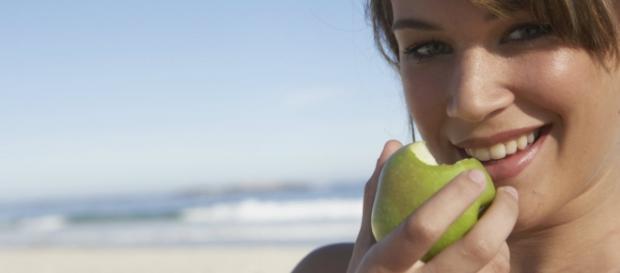 Mujer comiendo una manzana verde