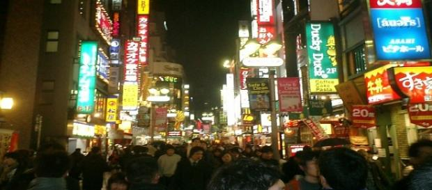 Calle de Tokio llena de gente por la noche.