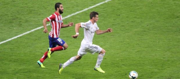 Bale y Arda Turan luchan por un balón en un derbi