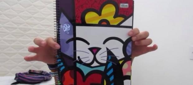 Garota mostra seu novo caderno