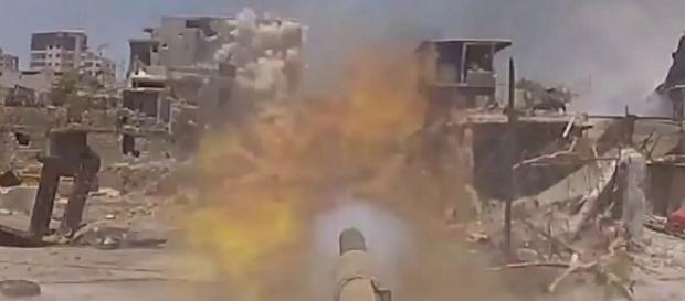 Ein Kampfpanzer der Regierungstruppen zerstört Stellungen der Rebellen. YT-Video: Сирия Реальный Бой с террористами на входе в Аль Кабун