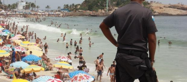Policial observa movimentação de banhistas em dia ensolarado de Ipanema