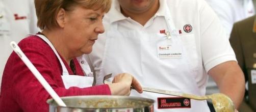 La Merkel in uno scatto insolito intenta ai fornelli.