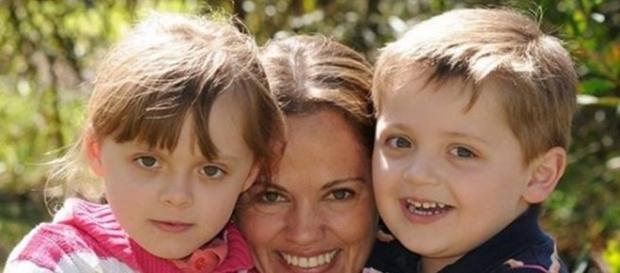 Na foto publicada em uma rede social, a mulher aparece contente ao lado dos dois filhos pequenos
