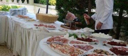 Cameriere spruzza insetticida sul buffet degli sposi