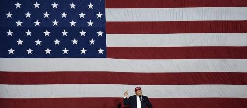 Donald Trump stands before American flag