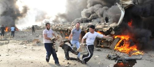 May 10, 2012: People run carrying a burnt body at the site of an explosion in Damascus