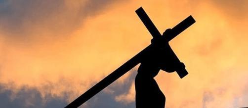 Imagem de um homem carregando uma cruz.