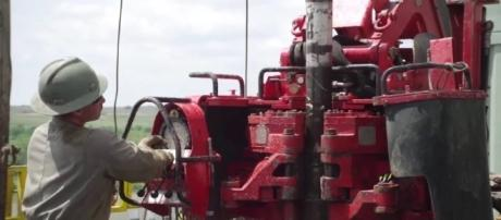 A worker adjusts settings on a fracking rig. YouTube (Screencap-Apache Corporation)
