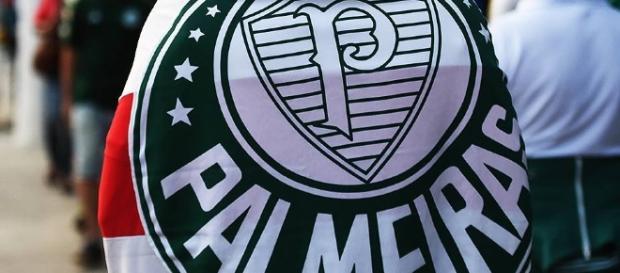 Torcedor do Palmeiras caminha com bandeira nas costas.