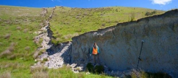 Dra. Kate Pedley posa em frente à muralha formada pelo terremoto (Crédito: YouTube/NewsNewZealand)